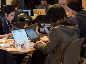 people working on their laptops at the hackathon