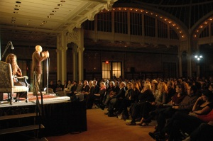 a StorySLAM speaker on stage while a full crowd listens intently